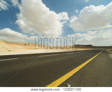 Asphalt road and sky with clouds in the Judean Desert.