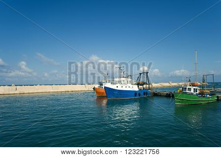 Fishing boats in the harbor on a background of blue sky.