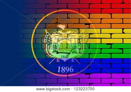 A well worn wall painted with a LGBT rainbow with the Utah state flag