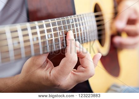 close up of acoustic guitar player's hands.