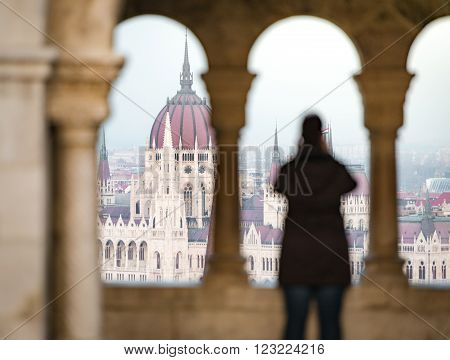 View on parliament building from fisherman bastion on Buda hill. Budapest Hungary Europe travel. Unrecognizable tourist in foreground taking photo.