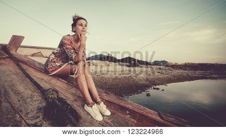 Young woman is sitting on the shipwreck and looking at the sunset. Artistic toning.
