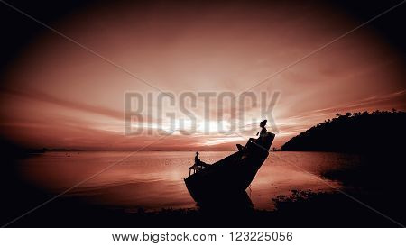Young couple on the sunken ship on the tropical sunset background.