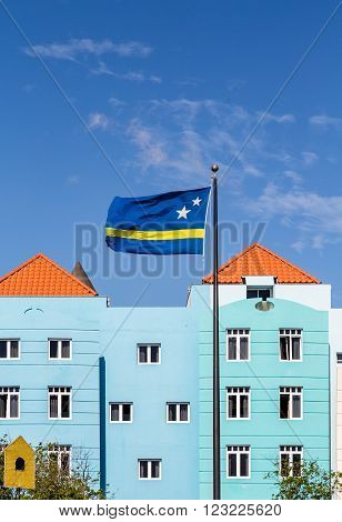 Curacao Flag by colorful buildings under nice skies