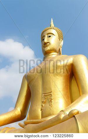 Golden statue of Buddha on blue sky background