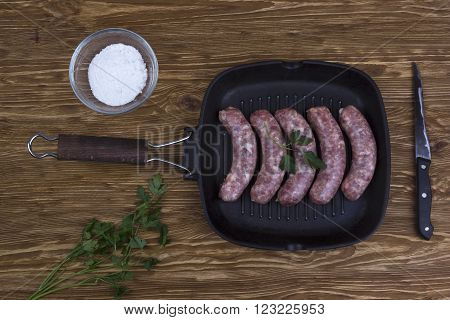 raw sausages on a  pan, salt and knife on wooden background