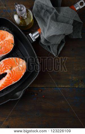 Raw Salmon Steak in steel griddle pan. Top view