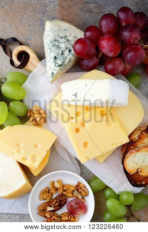 Different Types Of Delicatessen Cheeses With Grapes, Bread And Walnuts On The Slate Background
