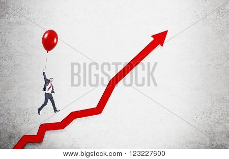 Businessman flying on red balloon over red graph drawn on concrete wall. Concept of career growth.