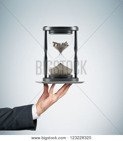 Hand holding tablet horizontally sand glass in dark wooden carcass on it'time' on top inside. Sand running. Concept of time
