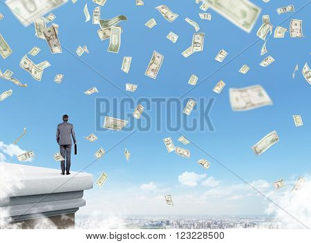 Businessman with case on roof dollars falling from above city view and blue sky. Concept of making money.