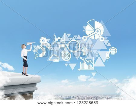 Businesswoman standing on roof throwing paper plane city view business icons and triangles on blue sky at background. Concept of starting new project.