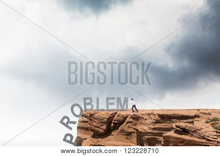 Businessman pushing letters of word 'problem' from rock. Cloudy sky at background. Concept of coping with problem.