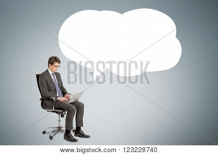 Businessman with laptop sitting on chair remark cloud to the right. Grey background. Concept of searching information.