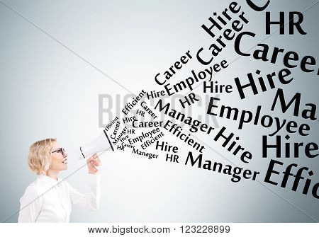 Businesswoman holding white loudspeaker many employment words from it. Grey background. Concept of informing.