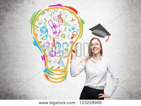 Young woman with finger up concidering education academic hat over her science icons in bulb drawn to the left. Concrete background. Concept of studying.