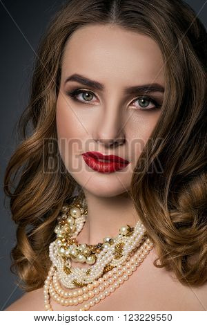 Beautiful girl with gold make-up and jewelery. Beauty face. Picture taken in the studio.