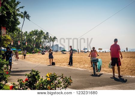 Waikiki, Honolulu, Hawaii, USA - December 13, 2015: The famous Waikiki Beach stretch and numerous visitors, with different activities on a cloudless, sunny afternoon. A sea spray gives the image a slight hazy look.