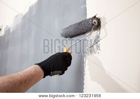 Renovation of interior. Man hand holds paint roller and painting wall with grey color.