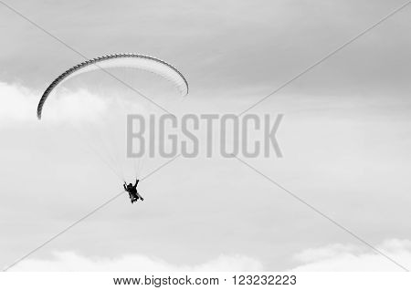 Paragliding in mountains in spring time. Blank space for a text. Black and white picture. Men on the left side. Georgia, Gudauri.