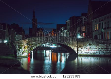cityscape of canal and bridge at night in Brugge, Belgium