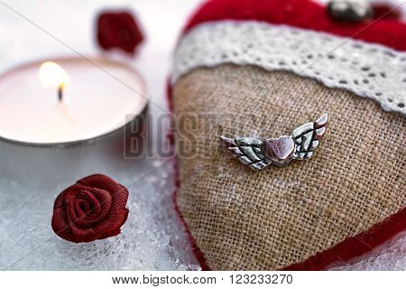 Romantic Valentine Plush Heart With A Winged Metal Heart On Ice Besides A Peaceful Tea Light Surroun