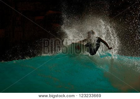 A backlit and silhouetted image of a surfer riding a blue wave.