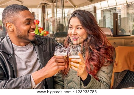 multi ethnic couple, afro-american guy and asian girl  drink beer in a romantic mood at an open restaurant - concept of interracial relationship