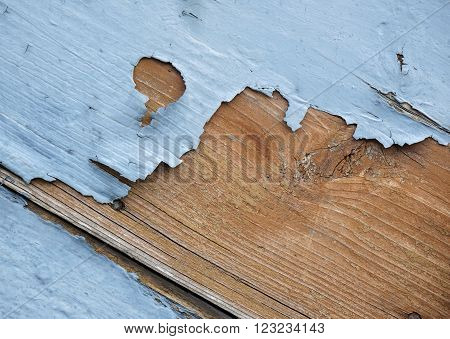 detail of blue flaking paint on wooden surface