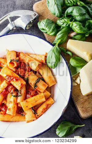 Italian and Mediterranean cuisine. Pasta Rigatoni with tomato sauce basil leaves garlic and Parmesan cheese. An old home kitchen with old kitchen utensils.