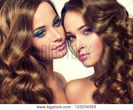 Two Beautiful  girls twins with long wavy hair .  Brunette  models  with curly hairstyle  and spring colorful makeup  . Cosmetics and  make up .