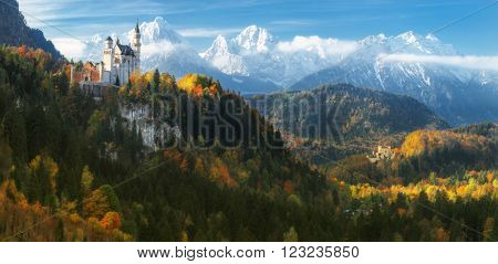 Germany. Panorama. The famous Neuschwanstein Castle and Hohenschwangau Castle on the background of snowy mountains and trees with yellow and green leaves.