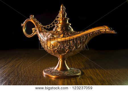 Aladdin's lamp isolated on wooden  brown  background