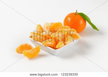 bowl of tangerine segments and whole tangerine on white background