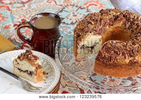 Bundt Cake sprinkled with cinnamon sugar and topped with pecans