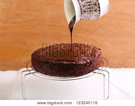 Pouring chocolate ganache out of jar over chocolate cake