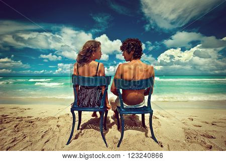 Beautiful loving couple sitting on chairs by the ocean .