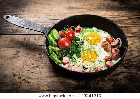 Morning meal- two fried eggs with sausages and fresh vegetables in old pan