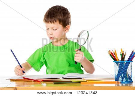 Inspired little boy at the table draw with pencils and magnifier in hands, isolated on white