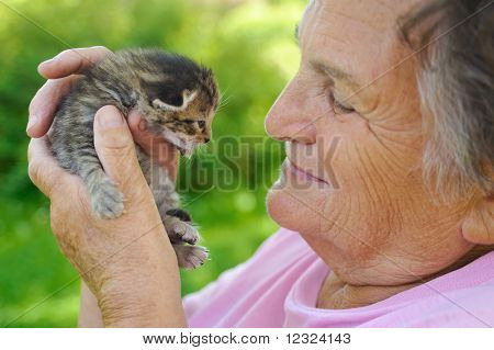 Senior woman holding kitten