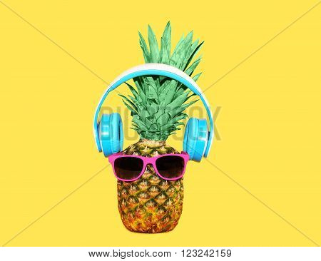 Fashion pineapple with sunglasses and headphones listens to music over yellow background, ananas concept photo