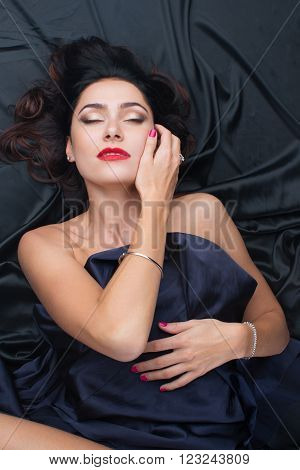 Sexy beautiful young woman lying on silk sheets, with eyes closed  evening make-up,  jewelry: earrings, rings, bracelets, nails bright red, hair spread on the bed, top view darck