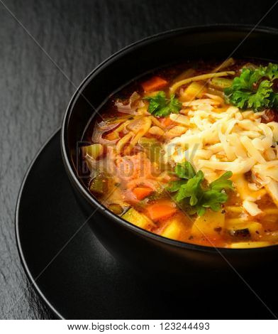 Minestrone -italian soup with vegetables. Black bowl on black board.