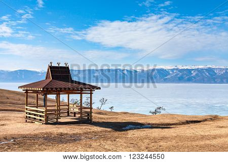 Traditional wooden gazebo in the Buryat-style on the shore of Lake Baikal in the winter mountains in the background. Winter Landscape on Olkhon island. Buryat region, Russia, Siberia.
