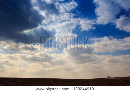 Blue Sky Cumulus Clouds Above Dark Ploughed Field