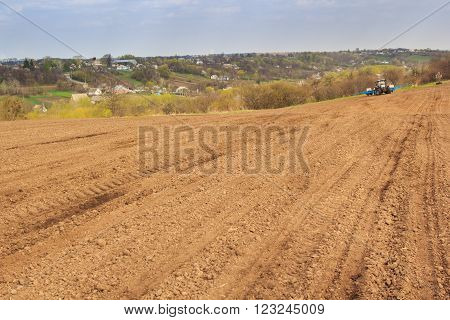 Tractor In Ploughed Field By Forest Ukrainian Village On Hills