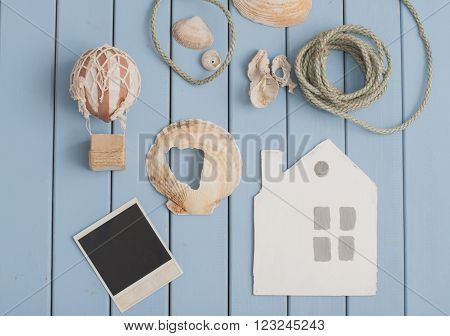 seashells polaroid picture vintage toy air balloon rope and cardboard house on blue wooden background