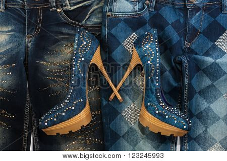 Glamorous women's fashion jeans shoes in rhinestones lying on jeans as background