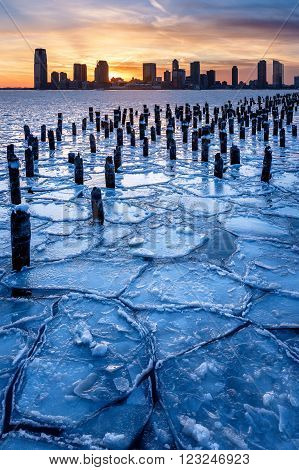 Winter view of the Frozen Hudson River with old wood pilings at sunset with Jersey City skycrapers