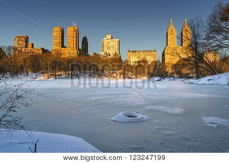 Winter sunrise on frozen Central Park Lake with view of the Upper West Side buildings. Manhattan, New York City